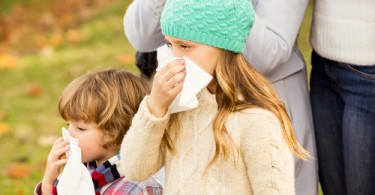 Sick family blowing their noses on an autumns day